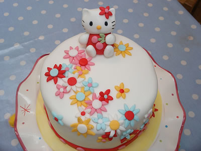 hello kitty on a bed of flowers cake